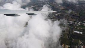 O avião durante a opinião superior da área da aterrissagem, da cidade e dos campos filme