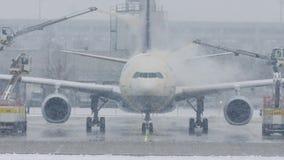 O avião em remove o gelo da almofada, degelando, aeroporto de Munich