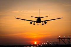 O avião está aterrando durante o nascer do sol Imagem de Stock