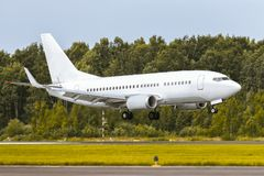 O avião está aterrando na pista de decolagem no aeroporto foto de stock royalty free