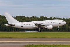 O avião está aterrando na pista de decolagem no aeroporto Fotos de Stock Royalty Free