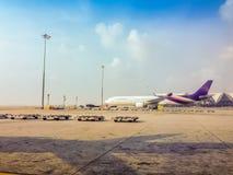 O avião está estacionando no campo para passageiros ao embarque ao avião antes que partida no voo da manhã em Suvarnab Fotos de Stock