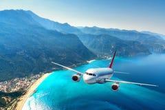 O avião está voando sobre montanhas surpreendentes com floresta e mar Imagem de Stock Royalty Free
