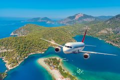 O avião está voando sobre montanhas surpreendentes com floresta e mar Fotos de Stock Royalty Free