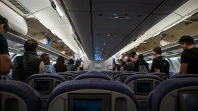 O avião interior, passageiros no corredor está andando para sair o avião fotografia de stock royalty free