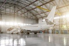 O avião no hangar, atrás do plano inteiro e do corredor central imagens de stock royalty free