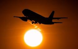 O avião no voo da decolagem através do disco solar, o motor sae de uma fuga do ar quente Imagem de Stock Royalty Free