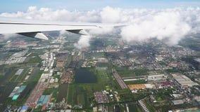 O avião voa através das nuvens acima da terra, estradas de cidade e os telhados são visíveis abaixo video estoque