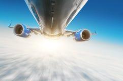 O avião voa sobre as nuvens no céu A vista da fuselagem, asas e motores, borrou a luz do movimento do efeito imagem de stock royalty free