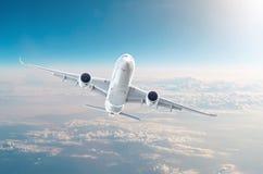 O avião widebody do passageiro está escalando o nível de voo alto no céu acima das nuvens Fotos de Stock
