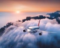 O avi?o do passageiro est? voando sobre nuvens no por do sol imagens de stock royalty free