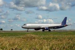 O avião branco move-se ao longo da pista de decolagem Imagem de Stock Royalty Free