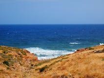 O azul brilhante do mar Cretan e a costa rochosa pitoresca perto do recurso de Rethymnon imagem de stock