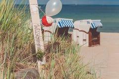 O azul colorido telhou cadeiras no Sandy Beach em Travemunde, Alemanha Balões bem-vindos Foto de Stock Royalty Free