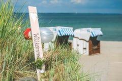 O azul colorido telhou cadeiras no Sandy Beach em Travemunde, Alemanha Balões bem-vindos Foto de Stock