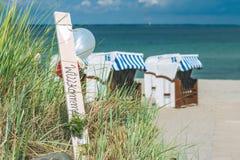 O azul colorido telhou cadeiras no Sandy Beach em Travemunde, Alemanha Balões bem-vindos Fotos de Stock