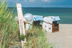 O azul colorido telhou cadeiras no Sandy Beach em Travemunde, balões bem-vindos germany Foto de Stock Royalty Free