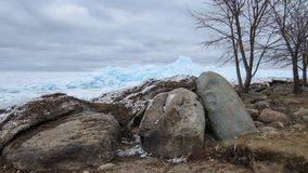 O azul coloriu o gelo que pressiona contra a linha rochosa da costa em um dia de inverno nebuloso Imagem de Stock Royalty Free