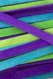 O azul, verde e o roxo coloriram o fundo das varas do picolé Imagens de Stock