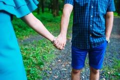 O azul vestiu os pares que andam junto por suas mãos imagens de stock