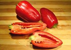 O búlgaro vermelho da pimenta de sino cortou na placa de madeira fotografia de stock royalty free