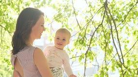 O babygirl de riso sorri com o mum no pátio traseiro verde slowmotion filme