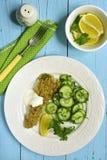 O bacalhau cozeu com os pães ralados do alho decorados com salada do pepino Fotos de Stock