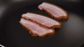 O bacon cai na frigideira video estoque