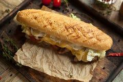 O baguette do trigo, lombinho de carne, grelhou o queijo real, tomate, i Fotografia de Stock