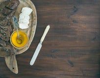 O baguette escuro fresco cortou nas fatias, no queijo do brie da cabra e no mel sobre Imagens de Stock