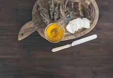 O baguette escuro fresco cortou nas fatias, no queijo do brie da cabra e no mel sobre Fotografia de Stock