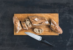 O baguette francês cortou em partes em uma placa de madeira rústica Fotografia de Stock Royalty Free