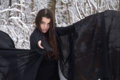 O bailado bonito novo da menina da mulher na floresta nevado do inverno estica para fora sua mão à parte dianteira foto de stock