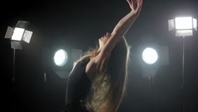 O bailado profissional da dança da bailarina nos projetores fuma na fase grande Moça caucasiano bonita com cabelo longo vídeos de arquivo