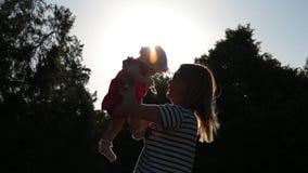 o Baixo-ângulo disparado, silhueta da mamã bonito nova que guarda sua filha infantil em seus braços abraça-a então contra a luz s vídeos de arquivo
