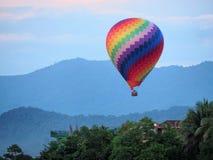 O balão de ar quente colorido decola e aumentar fotos de stock royalty free
