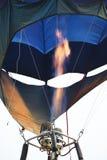O balão de ar quente colorido está voando no por do sol fotografia de stock