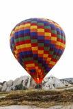 O balão de ar quente tira a flama à terra Fotografia de Stock
