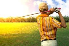 O balanço da batida do golfe do jogador dos homens dos jogadores de golfe disparou no curso no nascer do sol Imagens de Stock