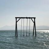 O balanço das crianças de madeira está no mar calmo azul sob o céu limpo aberto foto de stock royalty free