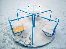 O balanço das crianças para a rotação em um círculo em um fundo vazio da neve fotos de stock