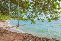 O balanço de madeira com cordas aproxima a praia Foto de Stock