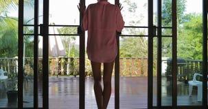 O balcão aberto da moça sai à opinião traseira da parte traseira do terraço, mulher loura na opinião da manhã da floresta tropica video estoque
