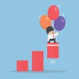 O balão do uso do homem de negócios levantou o gráfico Fotos de Stock Royalty Free
