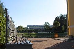 O banco barroco clássico no jardim verde e o lago ensolarado do verão na Catherine estacionam, Pushkin, St Petersburg Fotografia de Stock Royalty Free