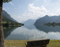 O banco de pedra e a vista panorâmica com montanhas refletiram na água Fotografia de Stock