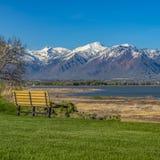 O banco quadrado no campo luxúria com uma vista de um lago e de uma neve elevando-se tampou a montanha fotos de stock royalty free