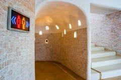 O banheiro bonito do tijolo com emplastro branco e o banheiro iluminam-se fotografia de stock