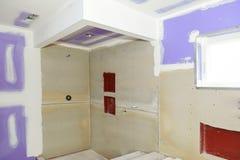 O banheiro remodela progride como o drywall é alisado, cobrindo emendas e parafusos com a fita imagens de stock royalty free