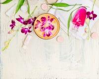 O banho com orquídea cor-de-rosa, a toalha, o creme e a loção com água rolam no fundo chique gasto branco, vista superior Foto de Stock